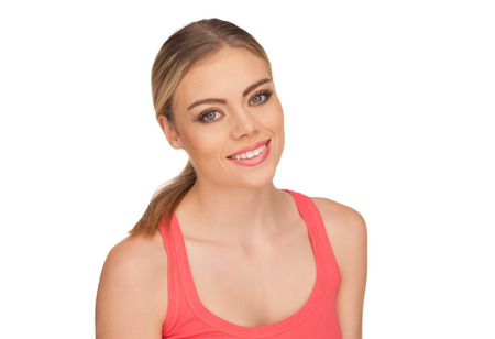 trustful: Portrait of an friendly blond woman with a warm smile wearing a red tank top on a white background