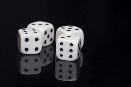 macro photo: Macro photo of four white dices over a black background and a mirror surface