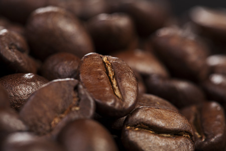 Coffee bean background with freshly roasted brown coffee beans, close up view with shallow dof and focus to a single bean