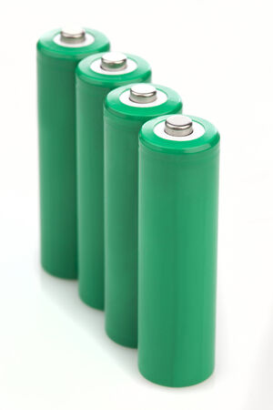 Upright line of four green batteries with blank covers conceptual of energy and cost saving rechargeable batteries, providing eco energy reducing possible pollution when normal batteries are discarded