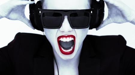open lips: Dramatic portrait of a woman or disc jockey in headphones and sunglasses yelling at the camera with her mouth open and trendy red sexy lips