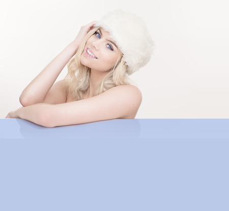 tantalising: Beautiful seductive blond woman in cool winter white wearing a fashionable fur hat and leaning on a blank blue placard with an enticing smile, copyspace for your text