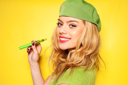 Trendy beautiful blond woman in a stylish green ensemble with an e-cigarette in her hand turning to smile at the camera, over yellow Stock Photo