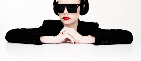 sexy headphones: Dramatic portrait of a sexy woman in sunglasses listening to music on a set of headphones leaning on a table looking at the camera