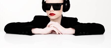 donna sexy: Ritratto drammatico di una donna sexy in occhiali da sole che ascoltano la musica su un set di cuffie che si appoggiano su un tavolo guardando la telecamera Archivio Fotografico