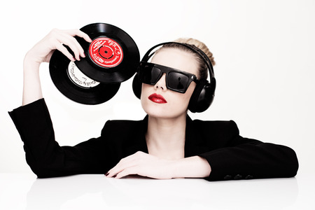 Beautiful glamorous sensual disc jockey wearing sunglasses and headphones and holding two vinyl records in her head, isolated on white