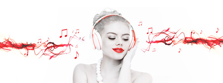 sensation: Artistic portrait of a beautiful woman wearing headphones listening to music with selective red colour and streaming music