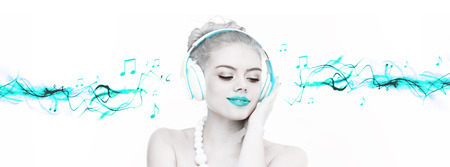 Beautiful woman enjoying her music listening to her headphones with a smile of bliss, artistic toned portrait with selective turquoise colour and streaming music 版權商用圖片