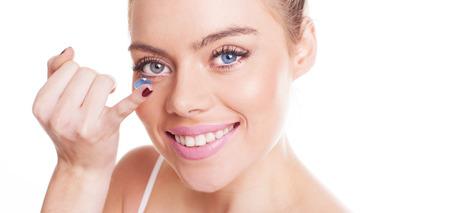 lentes de contacto: Mujer hermosa con una encantadora sonrisa amplia inserción de una lente de contacto en el ojo con el dedo, de cerca estudio tiro sobre el blanco