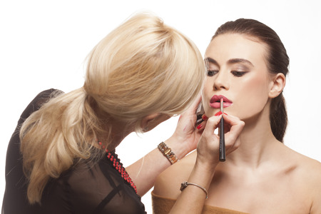 Beauty stylist applying lipstick to a beautiful young model with bare shoulders and long brunette hair, isolated on white photo