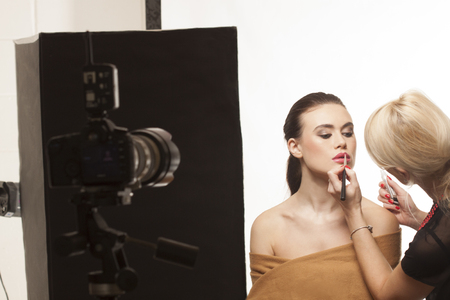 studio shoot: Beautiful stylish fashion model preparing for a studio photo shoot with a beautician touching up her lipstick and makeup Stock Photo