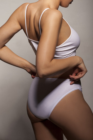 Sexy shapely woman with a tanned body wearing white underwear posing with her hands to her waist, close up side view of her torso