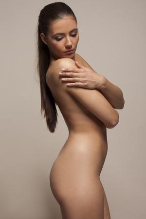 naked woman: Красивая скромный молодая женщина позирует обнаженной стоя боком, опустив глаза и скрестив руки на ее груди, студия портрет Фото со стока