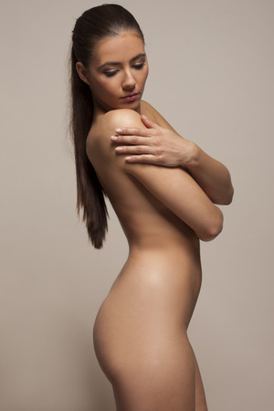 nude woman standing: Beautiful demure young woman posing nude standing sideways with downcast eyes and her arms crossed over her breasts, studio portrait