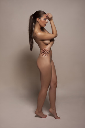 nude pose: Full length portrait of a beautiful nude woman standing sideways concealing her nipples with her arms raised elegantly on tiptoe