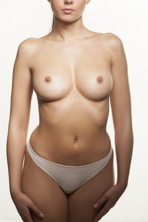 seni: Topless giovane donna in piedi di fronte alla telecamera in mutandine che mostrano i suoi seni e capezzoli sexy isolato su bianco