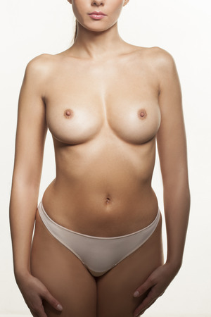 bare breast: Topless young woman standing facing the camera in panties displaying her sexy breasts and nipples isolated on white Stock Photo