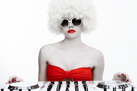 Portrait of a cool sexy female DJ wearing sunglasses and a white wig, behind the turntables and the buttons of the mixing system, on white background photo