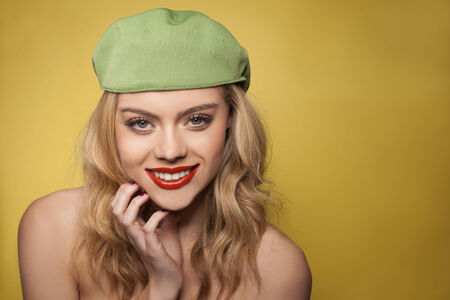Beautiful blond woman with a charming smile posing in a cute green cap with naked shoulders on a yellow background with copyspace photo