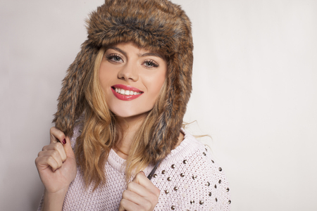 charmingly: Beautiful happy young woman in a furry winter hat holding the ear flaps and smiling charmingly at the camera with copyspace behind her as she stands sideways to the camera Stock Photo