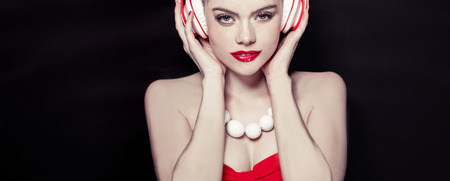 sexy headphones: Glamorous beautiful sexy woman wearing a red dress and lipstick listening to music on a set of headphones on a black background Stock Photo