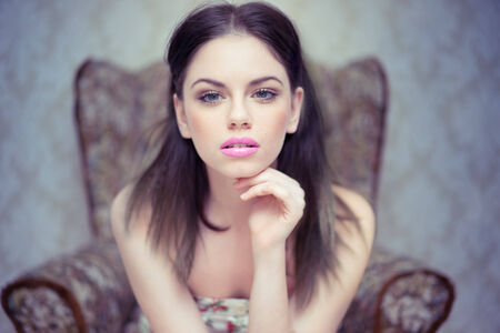 Beautiful dreamy young woman wearing makeup sitting forwards in an antique armchair looking into the camera photo