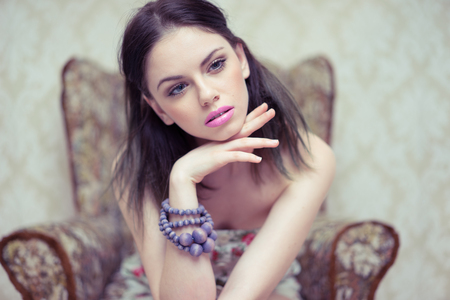 Elegant beautiful young woman with a dreamy look wearing modern jewellery daydreaming and staring off into the distance photo