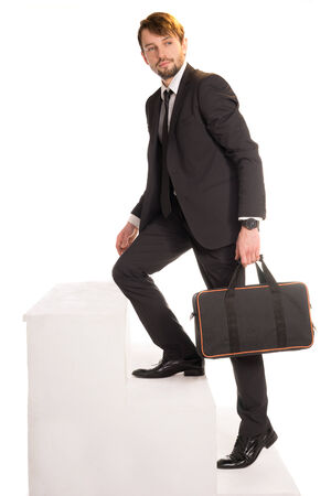 Handsome bearded stylish young businessman climbing stairs with a briefcase in his hand photo