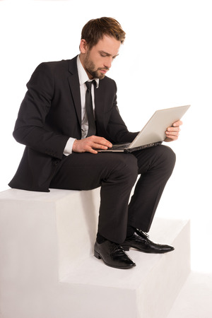 businessman working at his computer: Businessman sitting on a stair working on a laptop computer balanced on his lap browsing the internet for information and checking on his mail Stock Photo