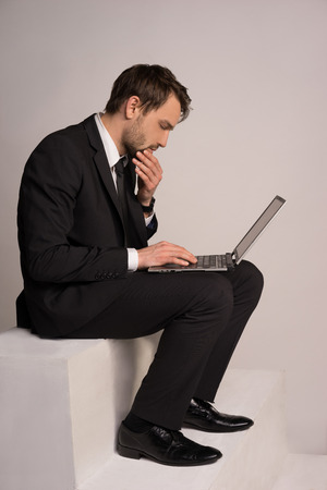Businessman sitting on a stair working on a laptop computer balanced on his lap browsing the internet for information and checking on his mail photo