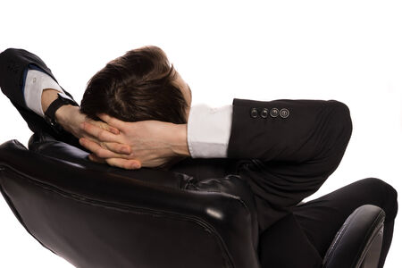 easy chair: Rear view of a young Caucasian relaxed businessman sitting in a comfortable leather office chair, with the hands clasped behind his head, on white background