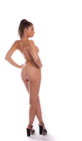 nude woman back: Sexy voluptuous woman posing nude standing with her back to the camera at an angle to show off her buttocks and breasts, isolated on white