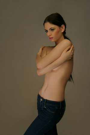 topless brunette: Studio shot of beautiful young woman wearing jeans, topless