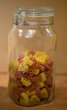 Dried multicolored heart-shaped pasta in a glass kitchen storage jar for traditional Italian cuisine, or a symbol of love photo