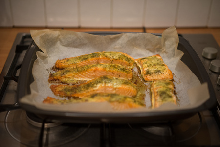 Preparing baked fish in a roasting pan with healthy fish fillets seasoned with herb garnish on oven paper photo