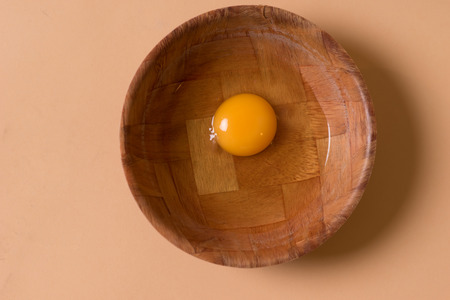 albumin: Overhead view of a healthy fresh raw egg with a deep yellow yolk in a mixing bowl waiting to be used as an ingredient in cooking or baking