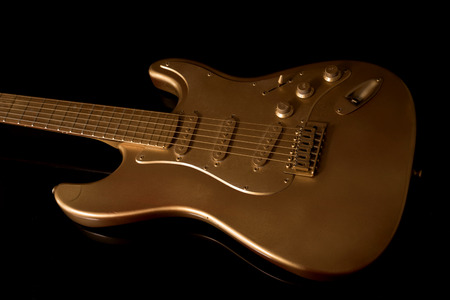 frets: Close up of a gold electric guitar on a dark background at an oblique angle with detail of the strings