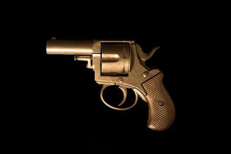Old hand gun revolver with an aged golden patina displayed sideways on a dark background with copyspace photo