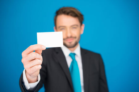 handsome businessman showing blank business card on blue photo
