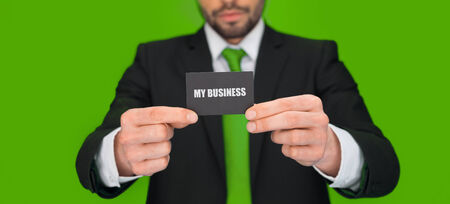 handsome businessman showing blank business card on green photo