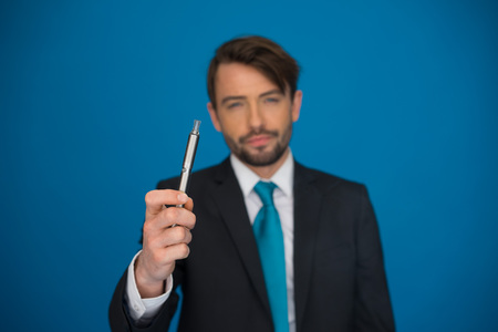 background e cigarette: handsome businessman with e-cigarette wearing suit and tie on blue background