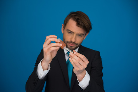 businessman topping up his e-cigarette with e-liquid on blue background photo