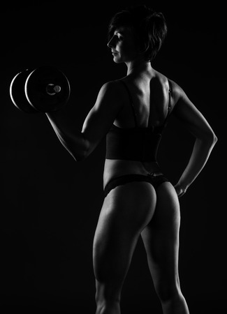 body curve: Dark portrait of a beautiful muscular sexy female body builder standing sideways in lingerie displaying her curvaceous buttocks while lifting weights