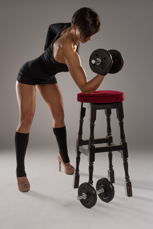 vintage chair: Athletic sexy woman with a muscular physique standing lifting weights in high heels and a leotard with her arm resting on a wooden bar stool