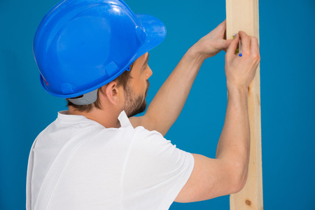 power operated: Carpenter or joiner marking a measurement with a pencil on a length of wood , view over his shoulder from behind, blue background Stock Photo