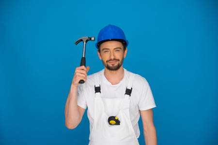 power operated: Smiling workman or builder wearing a hardhat and dungarees holding up a claw hammer in his hand on a blue background with copyspace