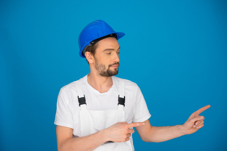 Upbeat enthusiastic young workman in dungarees and a hardhat pointing to the right of the frame with both hands, on blue with copyspace photo