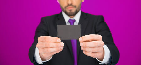 handsome businessman showing blank business card on pink photo