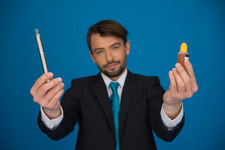 businessman holding e-cigarette and e-liquid on blue background photo