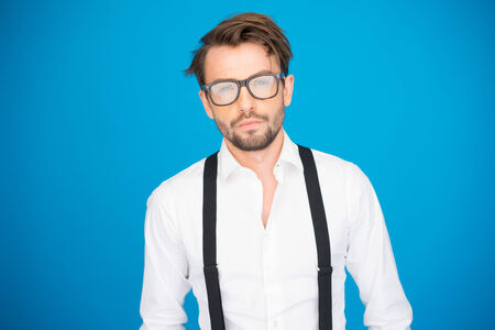 bearded: handsome man on blue wearing white shirt and braces on blue with glasses